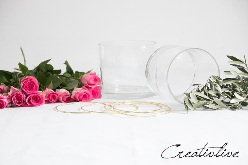 Glasvasen, Metallring und Rosen