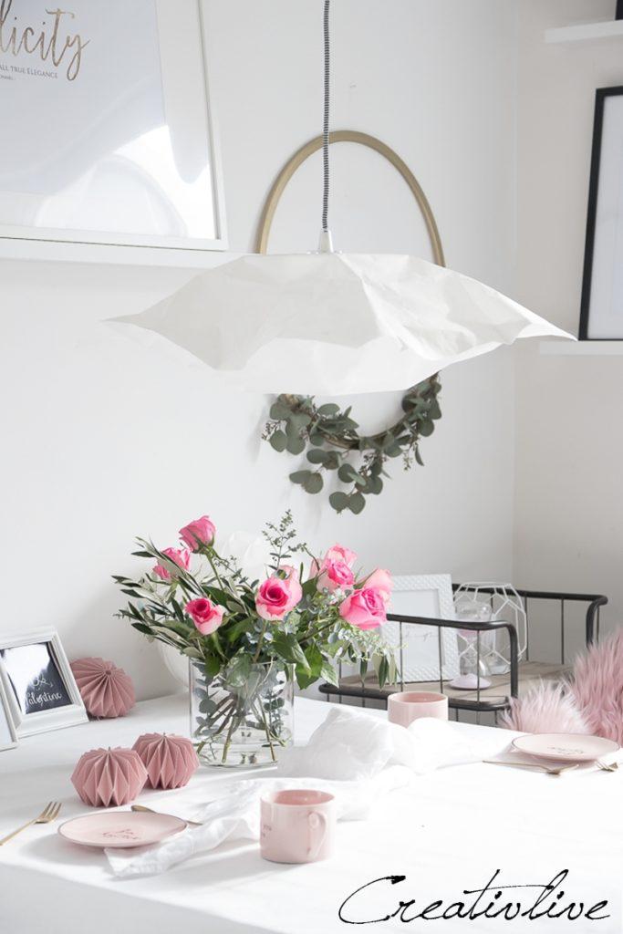 gedeckter Tisch mit rosa Geschirr und Rosen